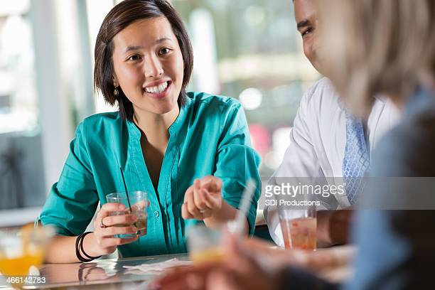 Asian woman with a group of people at a restaurant bar