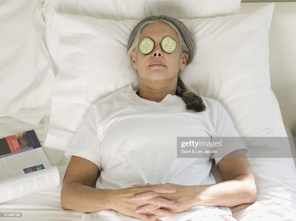 Asian woman with cucumber slices on eyes : Stock Photo