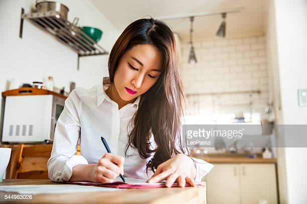 Asian woman working at home on contracts and mails