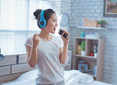 Asian women are listening to music and she sings in the room. happily