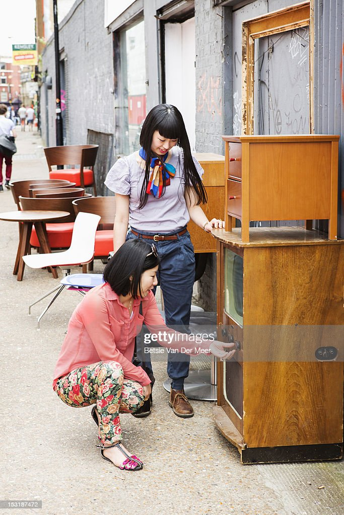 Asian women checking out an old tv at market shop. : Stock Photo
