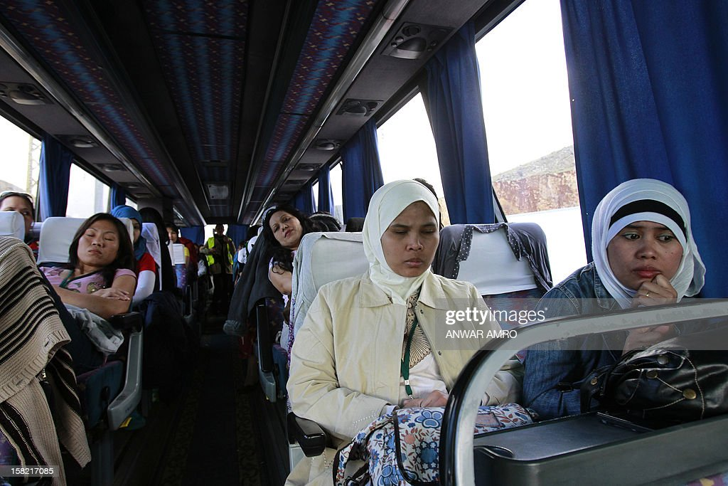 Asian women who were working in Syria are seen inside a bus after they left the war-torn country with the help of the International Organisation for Migration (IOM), on December 11, 2012 at the Lebanese border with Syria. The workers headed to Beirut International Airport from where they flew to their respective countries.