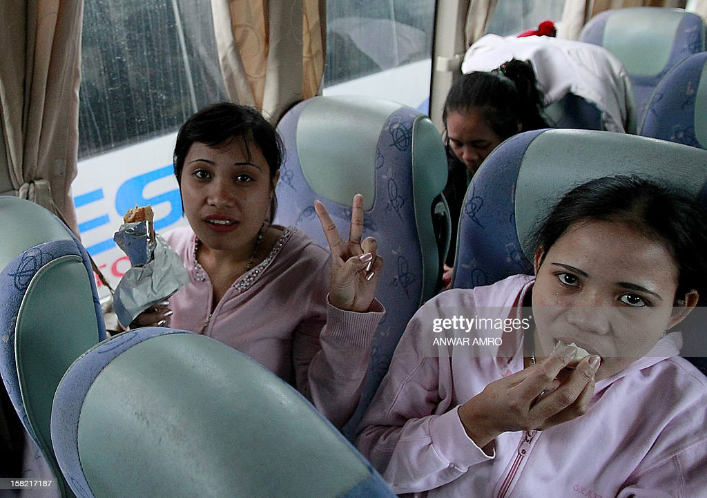Asian women who were working in Syria are seen inside a bus after they left the war-torn country with the help of the International Organisation for Migration (IOM), on December 11, 2012 at the Lebanese border with Syria. The workers headed to Beirut International Airport from where they flew to their respective countries. AFP PHOTO/ANWAR AMRO