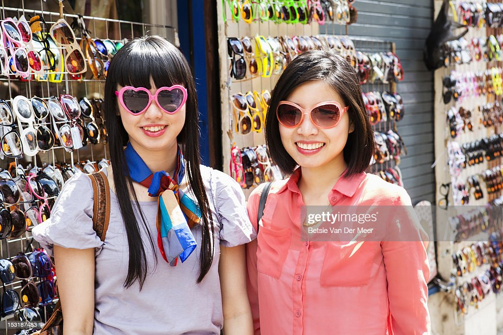 Asian women with chosen sunglasses at market stall : Stock Photo