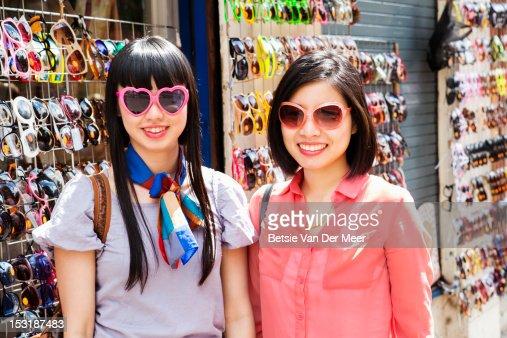 Asian women with chosen sunglasses at market stall : Stock Photo