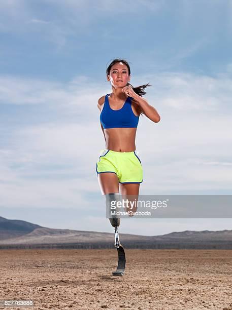 Asian Women With Prosthetic Leg Running In The Desert