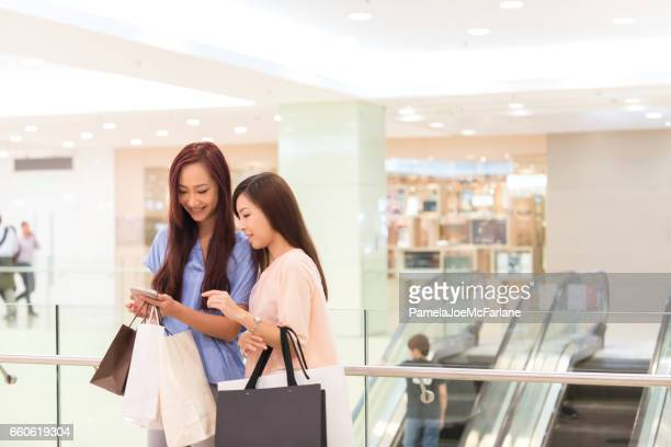 Asian Women with Shopping Bags Looking at Smartphone in Mall