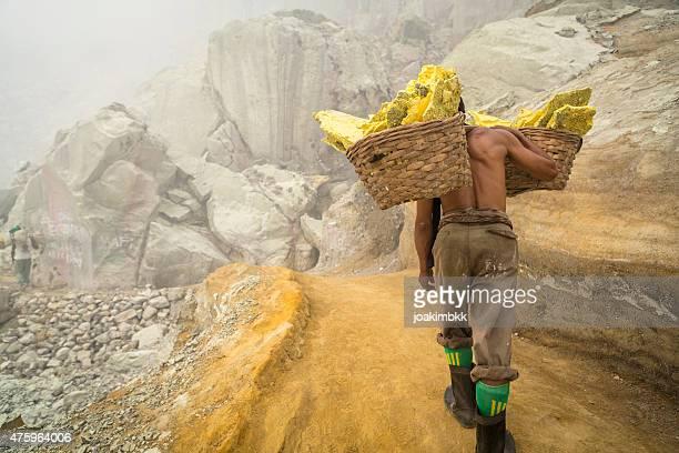 Asiatische Arbeiter tragen Körbe der Schwefel in Ijen-Vulkan