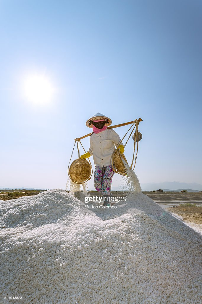 Asian worker in a salt pan with baskets, Vietnam