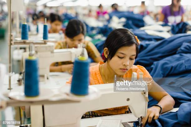 Asian worker sewing clothing in garment factory