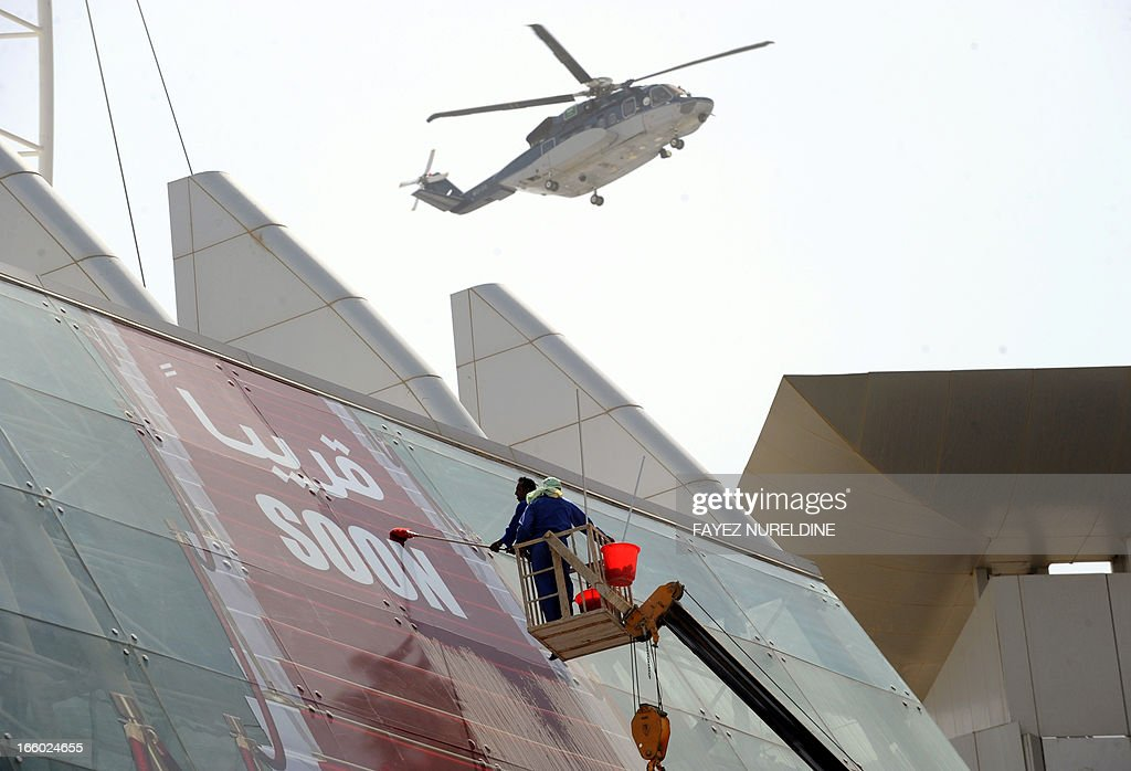 Asian workers clean the glass front of a highrise in the center of Saudi capital Riyadh on April 7, 2013. Saudi Arabia has given illegal foreign workers a three-month grace period to legalise their status, after panic over reported mass deportations, an official statement said.