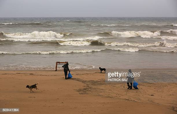 Asian workers collect rubbish from Beirut's public beach Ramlet alBaida on January 5 2016 AFP PHOTO / PATRICK BAZ / AFP / PATRICK BAZ