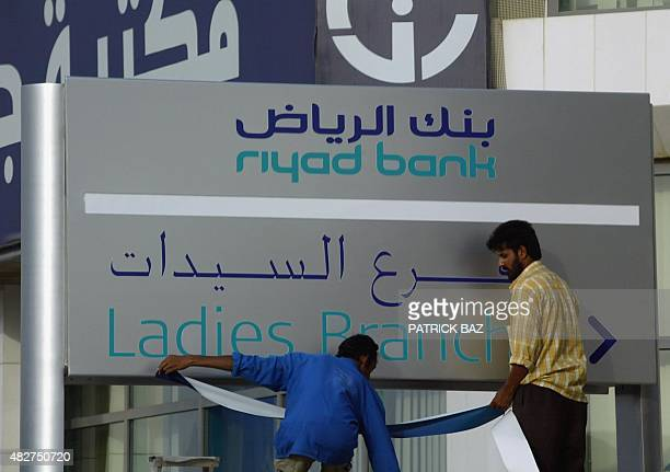 Asian workers fix a placard at the entrance of alRiyadh Bank branch which gives services only to women in the Saudi capital 13 July 2004 Saudi...