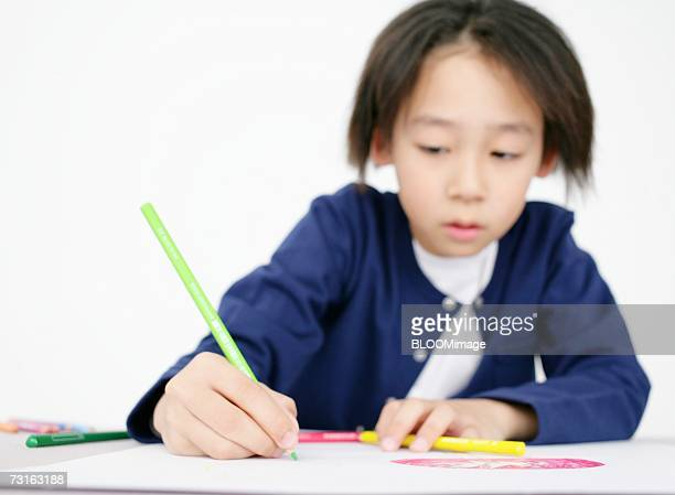 Asian young boy drawing picture on paper