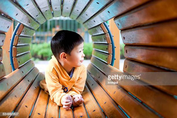 asian young boy happily playing in wooden toy