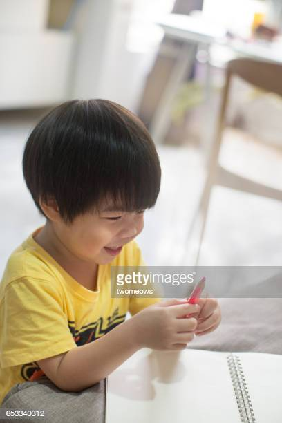 Asian young boy looking at colour pencil.