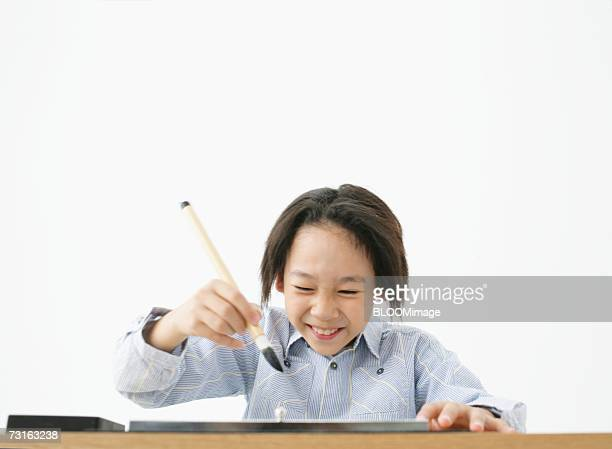 Asian young boy practicing  calligraphy