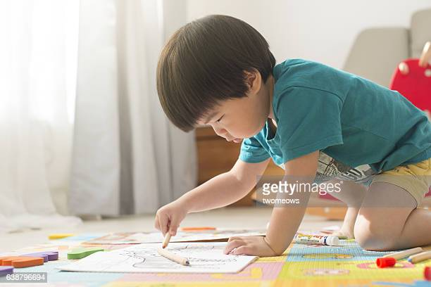 Asian young child colouring on floor.