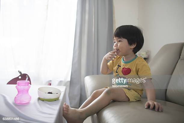 Asian young child snacking in domestic background.