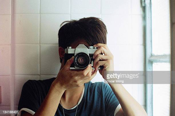 Asian young man is holding vintage camera