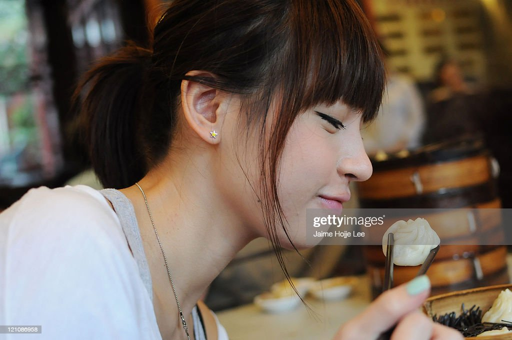 Asian young woman eating steamed dumplings : Stock Photo