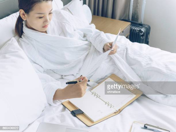 asian young woman in bathrobe examining files with laptop