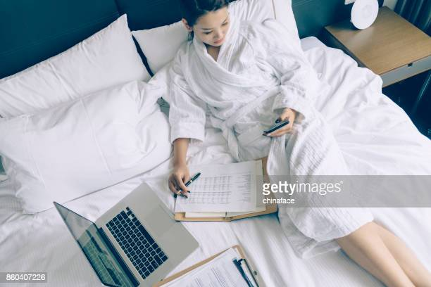 asian young woman in bathrobe working on bed with amrtphone and laptop