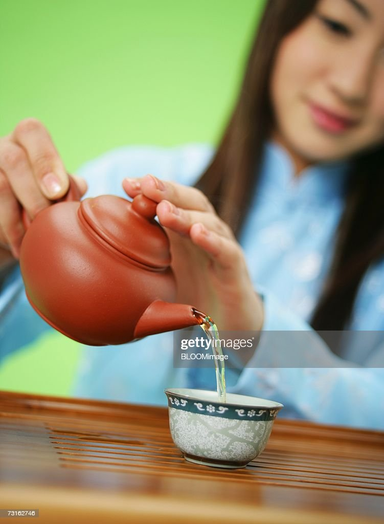 Asian young woman pouring tea from tea pot into tea cup : Stock Photo