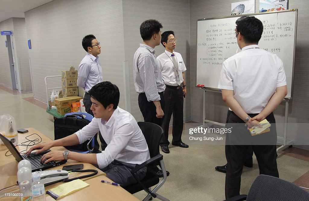 Asiana Airlines employees talk as the airline man an emergency room and phone line at the Incheon International Airport on July 7, 2013 in Incheon, South Korea. Two people are dead and more than 180 injured after an Asiana Airlines Boeing 777 aircraft coming from Seoul, South Korea crash-landed at San Francisco International Airport on July 6, 2013.