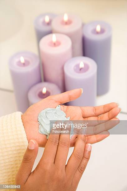 Asian/Indian young womans hands with facial scrub.