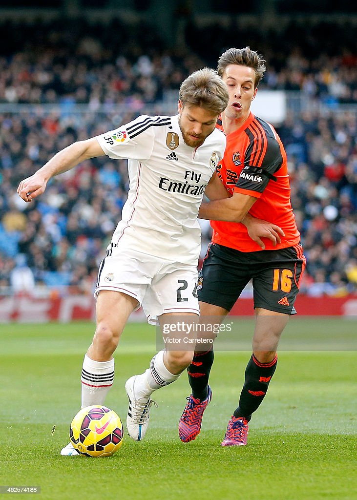 Asier Illarramendi (L) of Real Madrid competes for the ball Sergio Canales of Real Sociedad during the La Liga match between Real Madrid CF and Real Sociedad at Estadio Santiago Bernabeu on January 31, 2015 in Madrid, Spain.