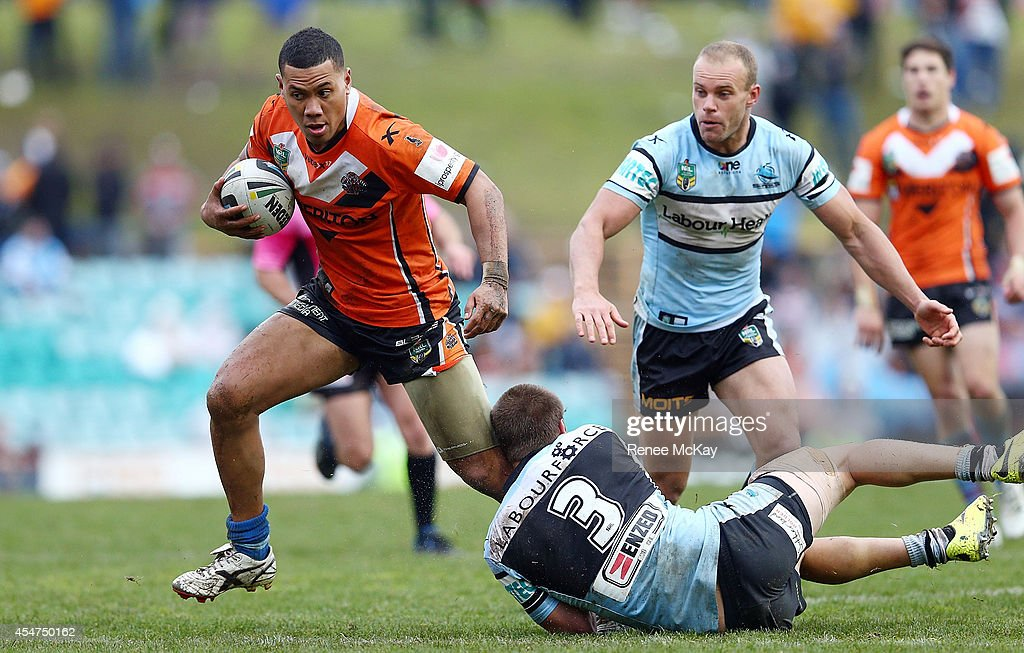 Asipeli Fine of the Tigers is tackled by Blake Ayshford of the Sharks during the round 26 NRL match between the Wests Tigers and the Cronulla Sharks at Leichhardt Oval on September 6, 2014 in Sydney, Australia.