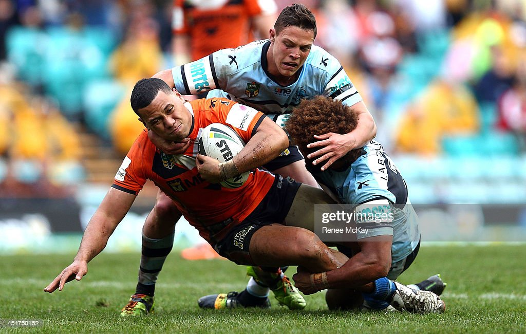 Asipeli Fine of the Tigers is tackled by Scott Sorensen and Sione Masima during the round 26 NRL match between the Wests Tigers and the Cronulla Sharks at Leichhardt Oval on September 6, 2014 in Sydney, Australia.