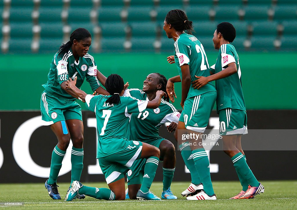 Asisat Oshoala (left) of Nigeria celebrates after scoring on a penalty kick against England during the FIFA U-20 Women's World Cup Canada 2014 Group C match between Nigeria and England at Commonwealth Stadium on August 13, 2014 in Edmonton, Canada.