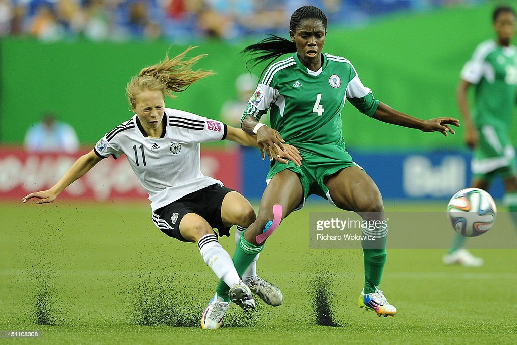 <a gi-track='captionPersonalityLinkClicked' href=/galleries/search?phrase=Asisat+Oshoala&family=editorial&specificpeople=9666335 ng-click='$event.stopPropagation()'>Asisat Oshoala</a> of Nigeria trips Theresa Panfil of Germany during the FIFA Women's U-20 Final at Olympic Stadium on August 24, 2014 in Montreal, Quebec, Canada. Germany defeated Nigeria 1-0 in overtime.