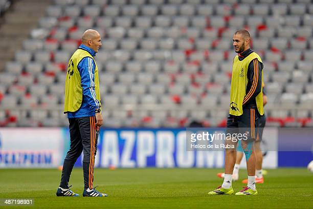 Asistant coach Zinadine Zidane speaks to Karim Benzema of Real Madrid during a training session ahead of their UEFA Champions League semifinal second...