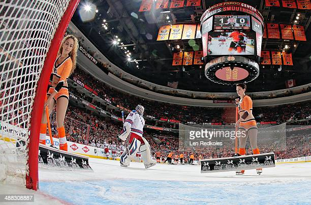 Asmaa Harakat and Kelsey Hoffman of the Philadelphia Flyers ice girls clean the ice during a stoppage in play with Henrik Lundqvist of the New York...