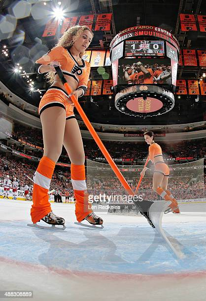Asmaa Harakat and Kelsey Hoffman of the Philadelphia Flyers ice girls clean the ice during a stoppage in play against the New York Rangers in Game...