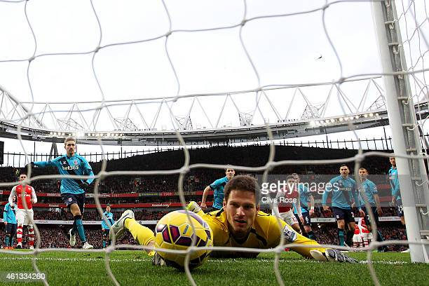 Asmir Begovic of Stoke City fails to stop the ball crossing the line as Alexis Sanchez of Arsenal scores his team's third goal from a freekick during...