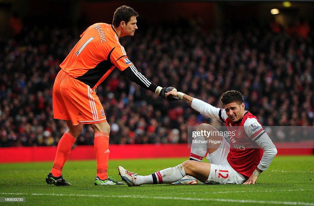 Asmir Begovic of Stoke City helps up Olivier Giroud of Arsenal during the Barclays Premier League match between Arsenal and Stoke City at Emirates Stadium on February 2, 2013 in London, England.