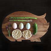 Asparagus, chilli, eggs and muffin on pig shape cutting board