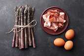Bunch of fresh purple asparagus, bacon and eggs in plates on rusty textured background