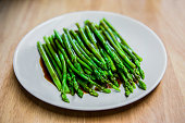 fresh asparagus in oyster sauce on white plate