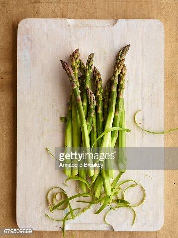 Asparagus pile with peeled stalks on light wood