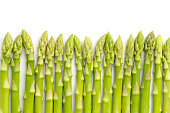A row of asparagus shoots on a white background.