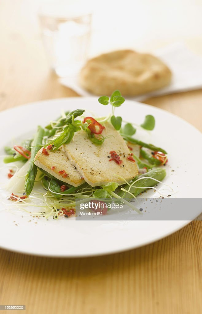 Asparagus salad and roasted tofu garnished with chili on plate : Stock Photo
