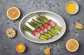 fresh green asparagus with bacon  in white bowl for baking on a gray background. view from above