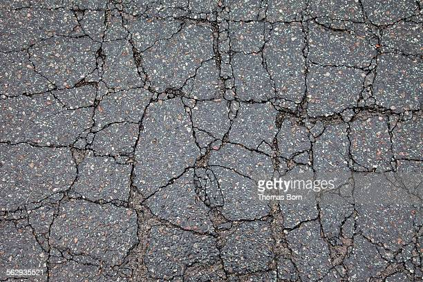 Asphalt cracked by frost and cold, potholes in Berlin, Germany, Europe