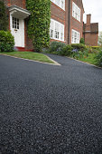 New asphalt tarmacadam driveway outside a beautiful brick house in London. Lots of copy space
