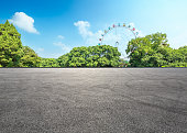 empty asphalt road and forest with playground ferris wheel